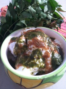 Dahi Vada topped with mint coriander chutney, tamarind chutney & chat masala powder