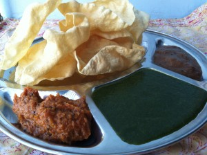 on top: papaRdum. left to right: tomato thakkali chutney, mint coriander chutney, tamarind chutney